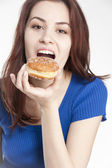 Young woman eating a donut — Stock Photo