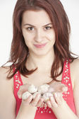 Young woman holding garlic in her hands — Stock Photo