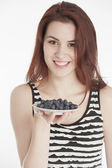 Young woman holding a plate with blueberries — Stock Photo