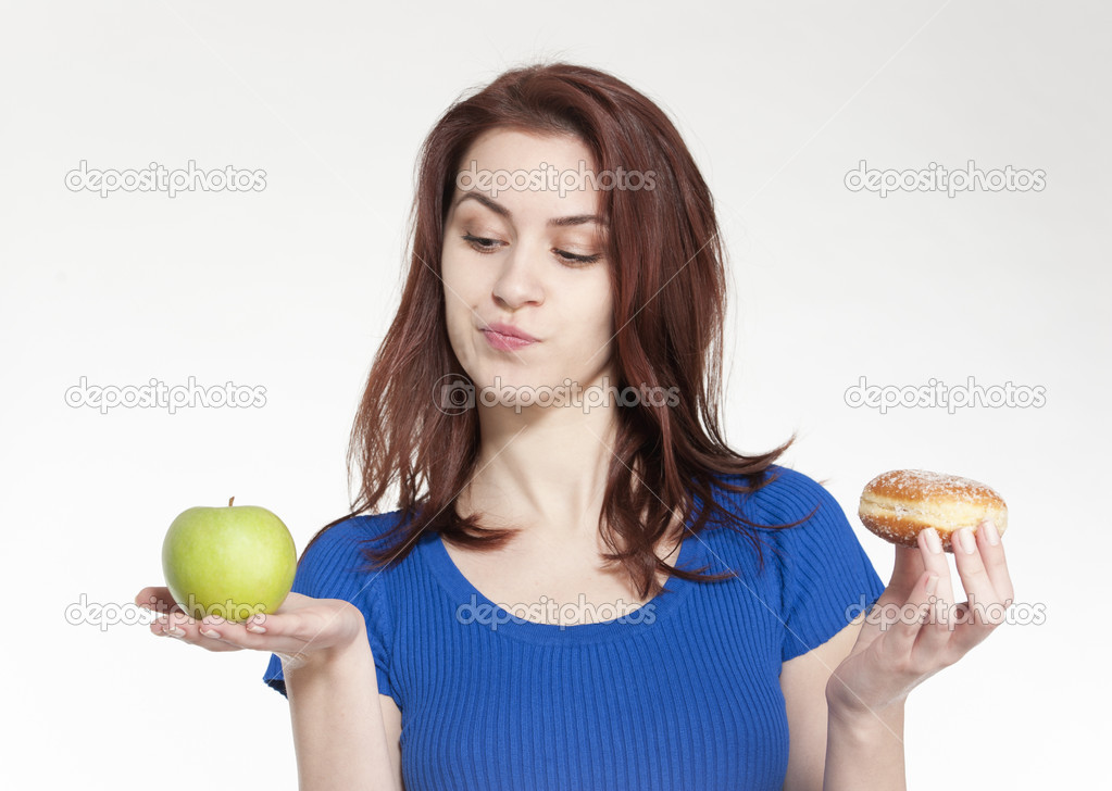 Young woman choosing between an apple and a donut — Stock Photo #8915437