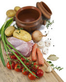 Ingredients for a roast chicken in a pot : chicken, potatoes, ca — Stock Photo