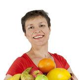 Una donna di mezza età sorridente felice tenendo un cesto pieno di frutta — Foto Stock