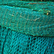 Coiled green fishing netting — Stock Photo #9424215