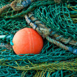 Green fishing netting with red buoy — Stock Photo