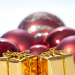 Golden christmas gifts and red christmas balls - Stock Photo