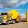 图库照片: Yellow Transport With Oilfield Tanks