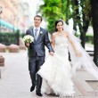 Stock Photo: Bride and groom having fun in old town