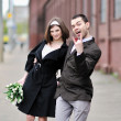 Stock Photo: Bride and groom having fun in an old town