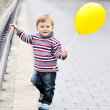Adorable little boy with yellow baloon in hand — Stock Photo