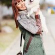 Stock Photo: Cheerful young woman playing with her puppy
