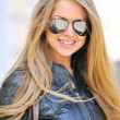 Pretty woman holding sunglasses - Stock Photo