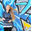 Stock Photo: Girl against grafitti wall