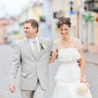 Happy bride and groom having fun in an old town — Stock Photo