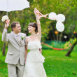 Happy bride and groom walking together in a park — Stock Photo