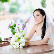 Happy young bride holding bridal bouquet — Stock Photo
