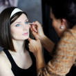 Stock Photo: Young beautiful bride applying wedding make-up by professional m