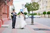 Bride and groom having fun in an old town — Stock Photo
