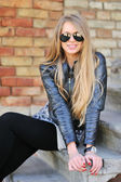 Stunningly beautiful young blond woman in a jacket and aviator sunglasses sitting on the stairs — Stock Photo