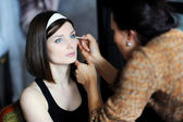 Young beautiful bride applying wedding make-up by professional m — Stock Photo