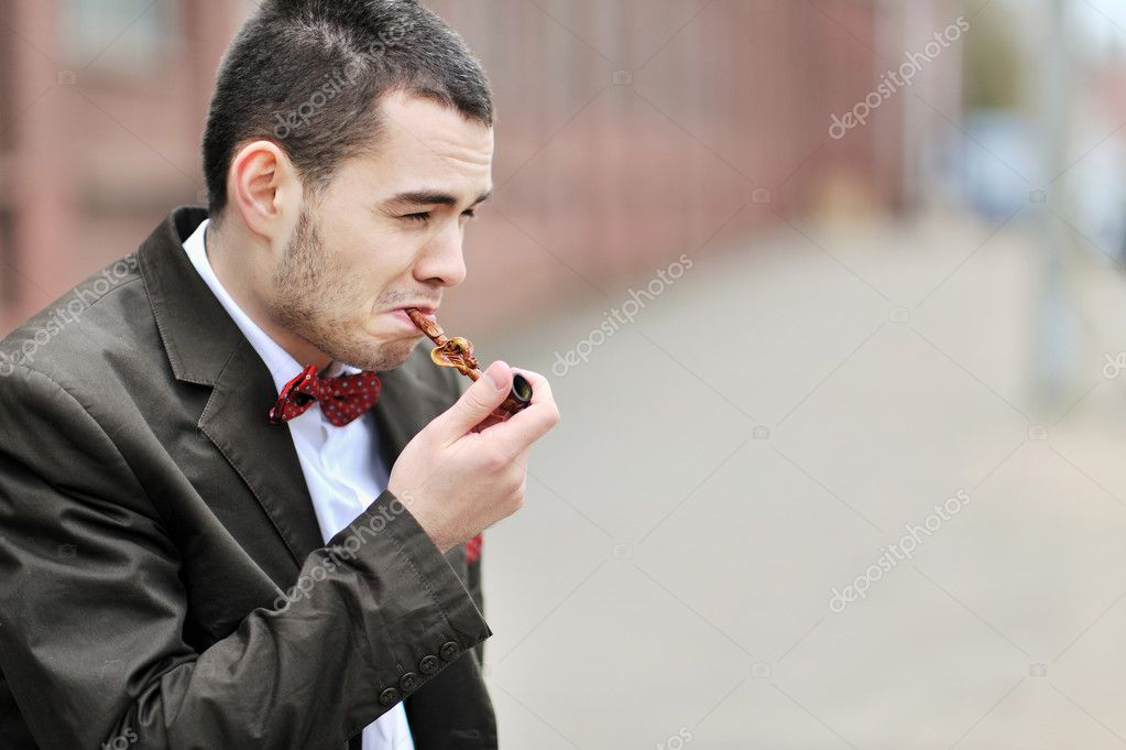 Young man smoking a pipe  Stock Photo #10037326