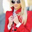Beautiful young blond woman in a red dress and sunglasses backli — Stock Photo