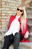 Young woman in red suit and sunglasses outdoor portrait — Stock Photo