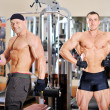Two bodybuilders posing in gym — Stock Photo