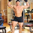 Stock Photo: Bodybuilder flexing his muscles in gym and smiling