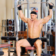 Stock Photo: Young bodybuilder training in the gym. Back muscles, front wiew
