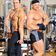 Two bodybuilders posing at the gym — Stock Photo