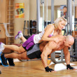 Bodybuilder is doing push-ups with his female co-worker behind t — Stock Photo