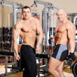 Two bodybuilders pose and show thumbs up on training in the hall — Stock Photo