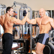 Bodybuilders shake each others hands at the gym after a workout — Stock Photo