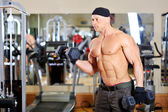 Bodybuilder shakes his biceps with dumbbell — Stock Photo