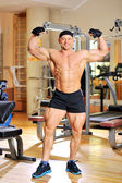 Bodybuilder flexing his muscles in gym and smiling — Stock Photo