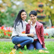 Happy mother with her daughter sitting on a grass outdoors — Stock Photo