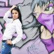 Beautiful girl posing against grafitti wall - Stock Photo