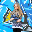 Beautiful woman with arms crossed against graffiti wall — Stock Photo