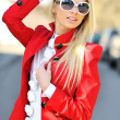 Beautiful young woman in sunglasses posing outdoors — Stock Photo