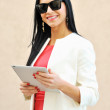 Young beautiful brunette holding tablet pc and smiling — Stock Photo #10386063