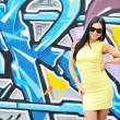 Beautiful young woman in sunglasses posing against graffity wall — Stock Photo