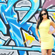 Beautiful young woman posing against graffity wall — Stock Photo