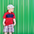 Adorable little boy looking at copyspace on green background - Stock Photo