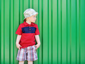 Adorable little boy looking at copyspace on green background — Stock Photo