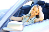 Young beautiful woman in her new car - Closeup — Stockfoto