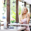 Cute beautiful girl sitting at a table in the restaurant and fli — Stock Photo