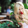 Girl smelling a rose - Stock Photo