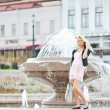 Stock Photo: Beautiful young woman posing by the fountain in the old town