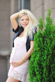 Pretty pregnant girl touching her tummy and posing outdoors — ストック写真