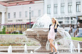Beautiful young woman posing by the fountain in the old town — Stock Photo